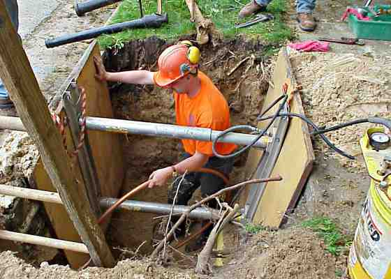 Worker replacing lead pipes in Madison